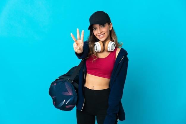 Giovane donna sportiva con borsa sportiva isolata sulla parete blu felice e contando tre con le dita
