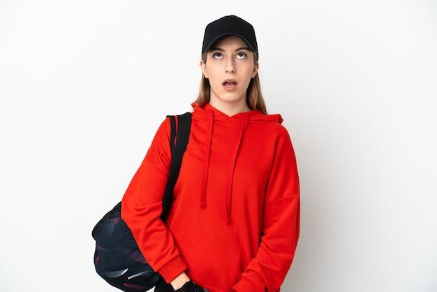 Giovane donna sportiva con borsa sportiva isolato su sfondo bianco, alzando lo sguardo e con espressione sorpresa