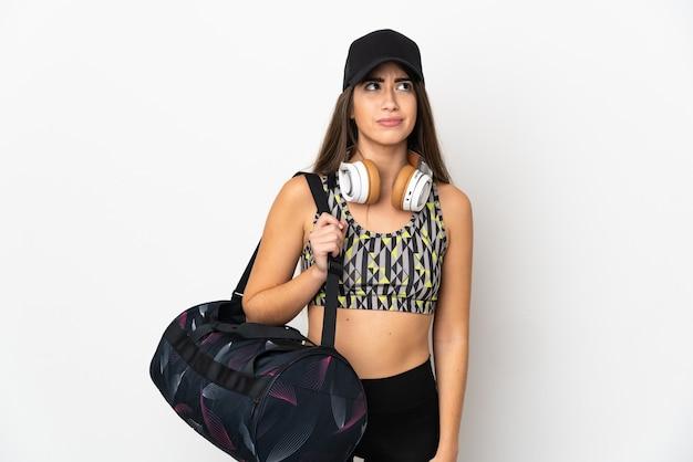 Giovane donna sportiva con borsa sportiva isolato su sfondo bianco e alzando lo sguardo