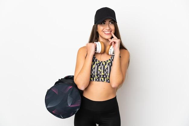 Giovane donna sportiva con borsa sportiva isolato su sfondo bianco pensando un'idea mentre cerca
