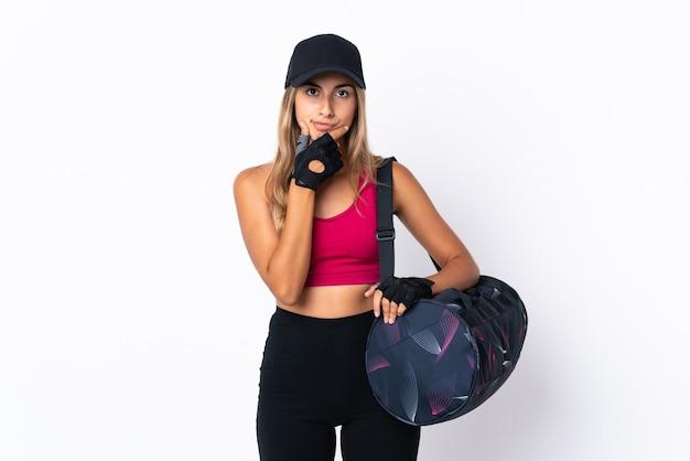 Giovane donna sportiva con borsa sportiva sopra il pensiero bianco isolato della parete