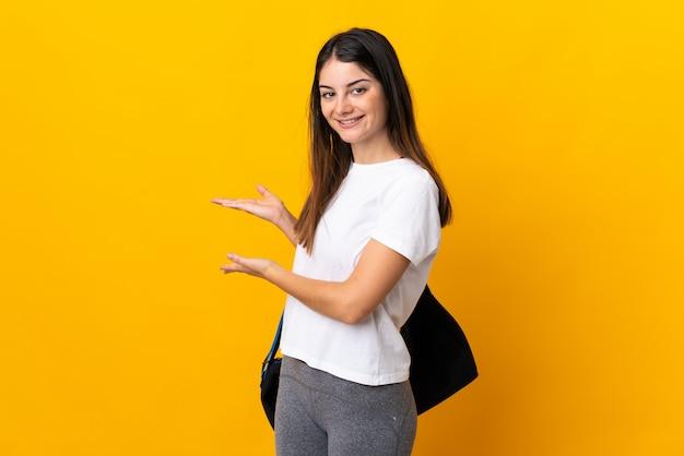 Giovane donna sportiva con borsa sportiva isolata su giallo allungando le mani al lato per invitare a venire