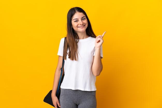 Giovane donna sportiva con borsa sportiva isolata sulla rappresentazione gialla e alzando un dito in segno del meglio