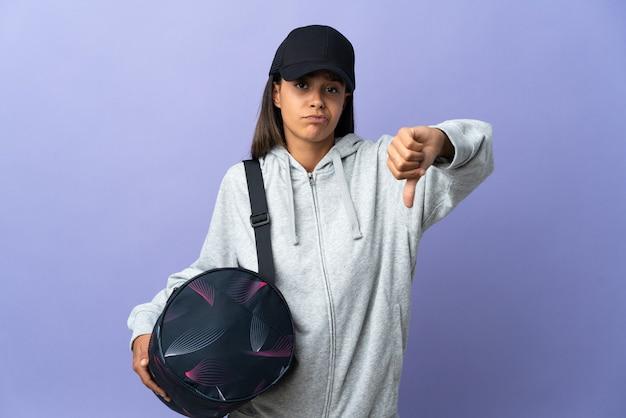 Giovane donna sportiva con borsa sportiva che mostra il pollice verso il basso con espressione negativa