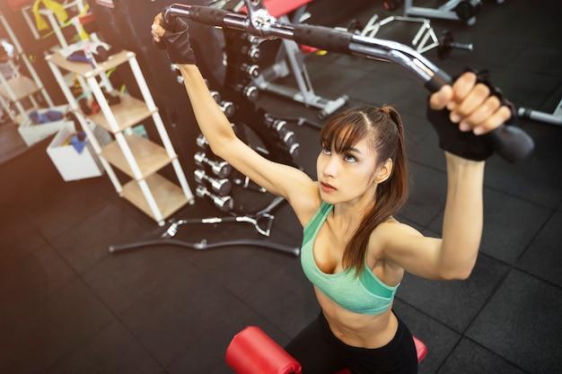 Giovane donna sportiva allenandovi in palestra
