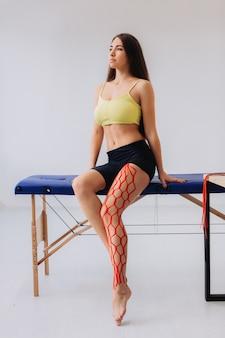 Giovane atleta femminile allegra che tiene la gamba ferita dopo il trattamento con nastro kinesio.