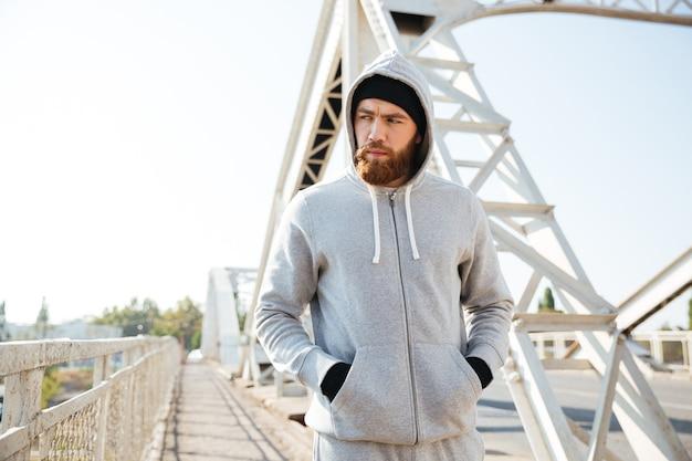 Giovane sportivo in cappuccio che cammina lungo il ponte urbano al mattino