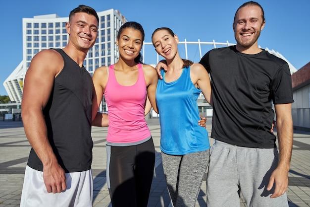 Giovani sportivi che si abbracciano sullo sfondo del paesaggio urbano