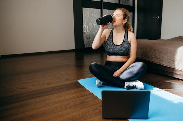 Giovane donna allegra acqua potabile dopo allenamento a casa