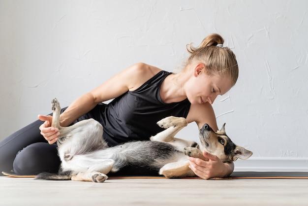 Giovane donna sportiva che abbraccia il suo cane di razza mista