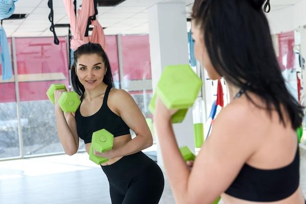 Donna giovane e sportiva che si esercita in palestra con manubri
