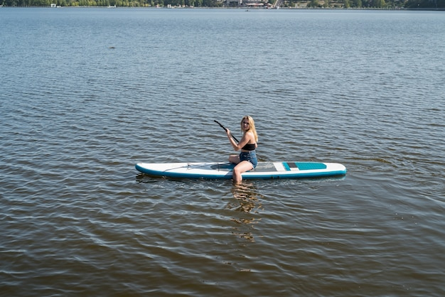 Giovane donna sportiva che si trova e si rilassa sull'acqua blu dello stagno della tavola da sup. vacanze estive