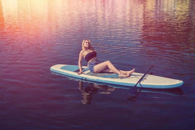 Giovane donna sportiva che si trova e si rilassa a bordo dell'acqua blu dello stagno sup. vacanze estive