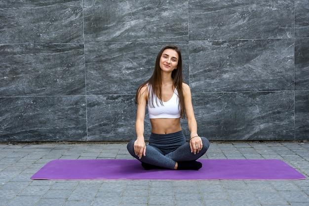 Giovane donna sportiva in posa sul paesaggio urbano. è molto carina e magra