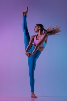 Giovane donna sportiva che si allena isolata su sfondo sfumato per studio in luce al neon atletica e
