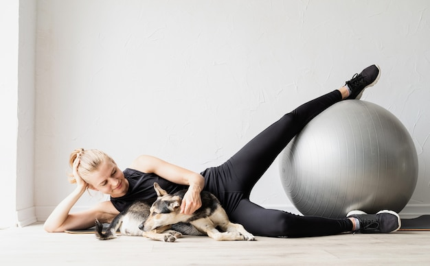 Giovane donna sportiva che si allena sulla palla fitness a casa