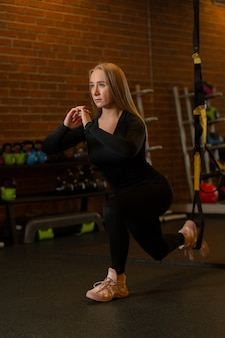 La giovane donna bionda sportiva in uniforme sportiva nera e crosing beige fa gli affondi calciati in avanti e guarda dritto in palestra tra i manubri.