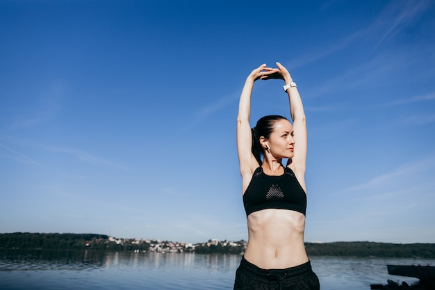 La giovane donna di forma fisica di sport fa l'allungamento degli esercizi alla musica d'ascolto all'aperto della spiaggia con le cuffie.