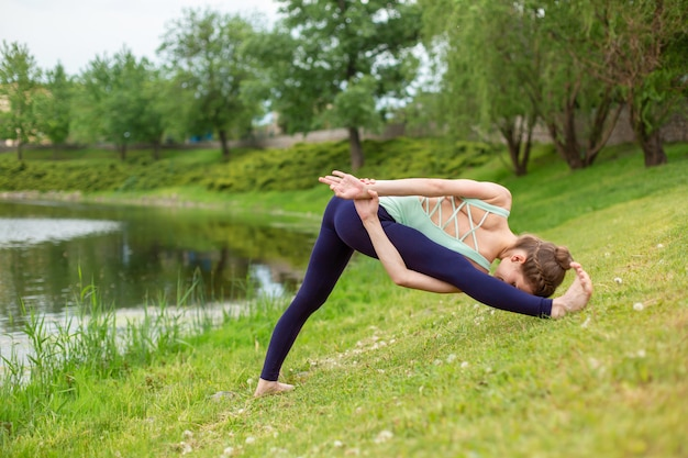 Una giovane ragazza sportiva pratica yoga su un prato verde vicino al fiume