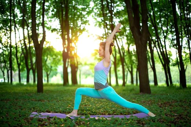 La giovane ragazza di sport pratica lo yoga in una postura di asana di yoga della foresta di estate verde chiusa