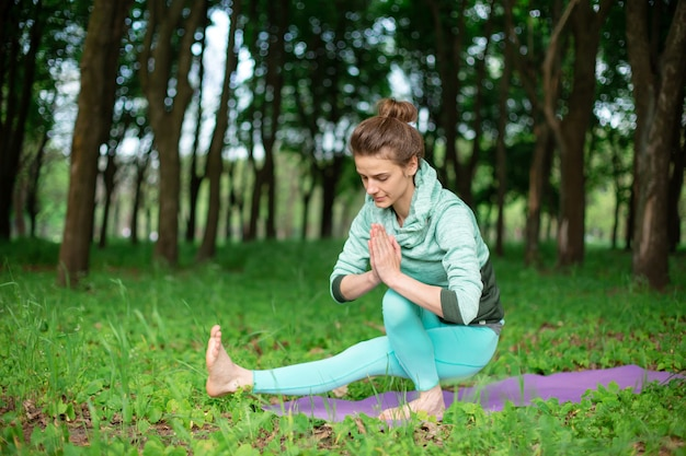 La giovane ragazza di sport pratica lo yoga in una postura di assana di yoga della foresta di estate verde chiusa