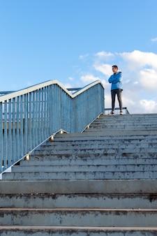 Un giovane sportivo sta in cima al ponte di osservazione e guarda in lontananza. il concetto di superare le difficoltà, salire verso l'alto. vista verticale.