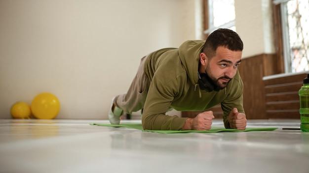 Giovane uomo di sport che fa esercizio di plancia di gomito in palestra vuota con palline gialle dietro di lui tutto dentro