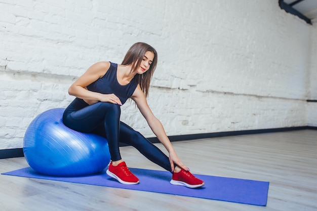 Giovane donna sportiva che fa esercizi con la palla su un tappetino in palestra