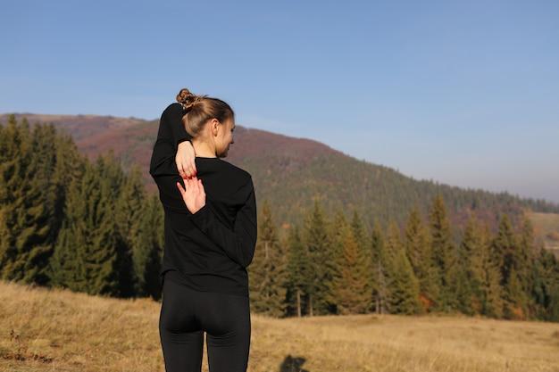 La giovane donna di sport che fa l'yoga si esercita sulle montagne e sul cielo in autunno