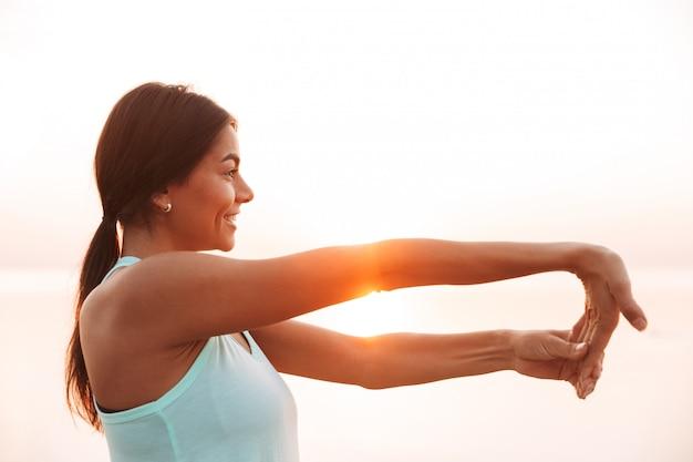 La giovane donna di sport all'aperto sulla spiaggia fa gli esercizi di sport