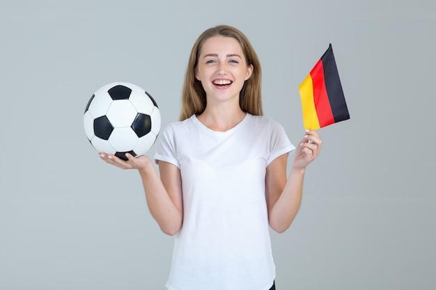 La giovane donna di sport con un pallone da calcio e la bandiera della germania su luce