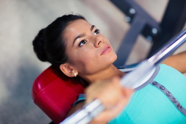 Giovane donna sportiva allenamento con bilanciere in panchina in palestra