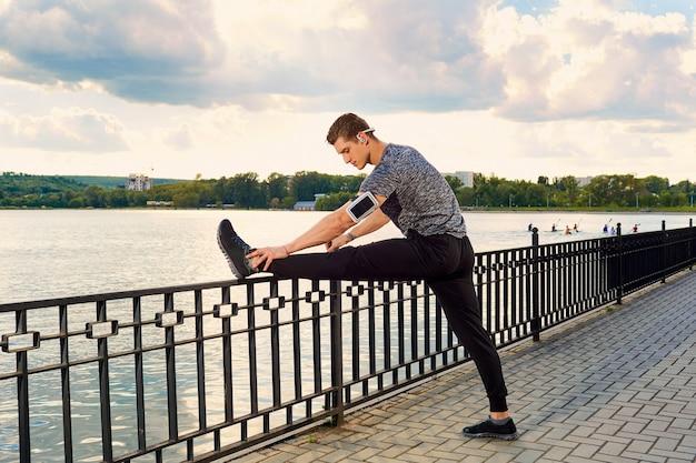 Giovane corridore sportivo che allunga le gambe prima della corsa