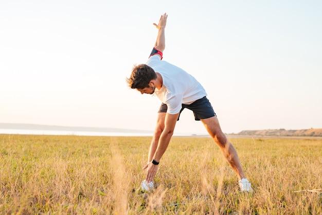 Giovane sportivo in piedi e che si estende all'aperto al mattino