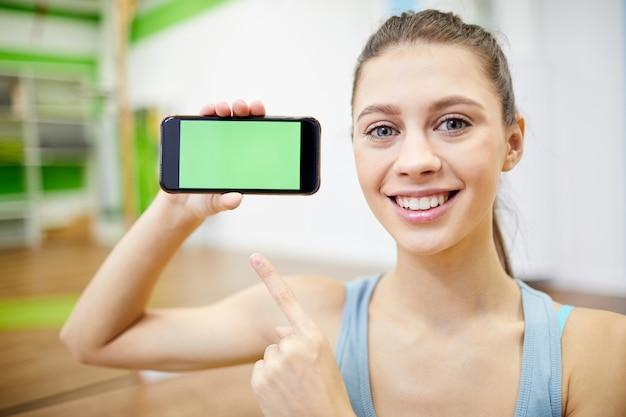 Giovane sportiva che tiene smartphone
