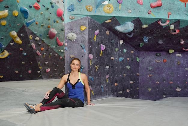 Giovane sportiva stanca dopo un duro allenamento seduto sul tappeto vicino a una delle pareti da arrampicata e ti guarda in pausa
