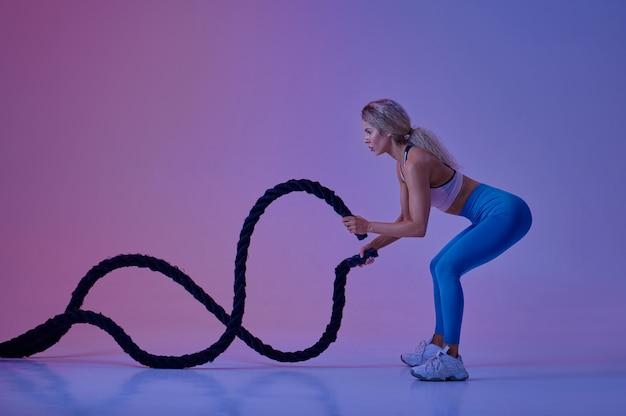 Giovane sportiva con corde posa in studio, sfondo al neon, crossfit