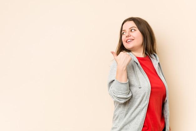 La giovane donna curvy sportiva indica con il dito pollice lontano