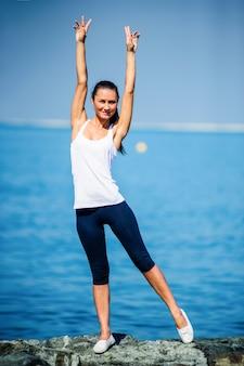 Giovane ragazza sportiva che gode del suo tempo sulla spiaggia