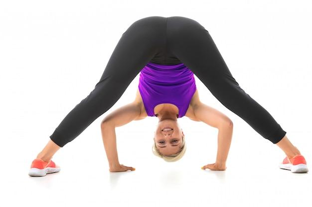 La giovane ragazza sportiva con i capelli chiari in un argomento sportivo nero, leggings neri e scarpe da ginnastica luminose fa esercizi.
