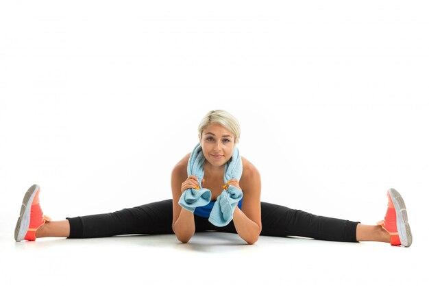 La giovane ragazza sportiva con i capelli chiari in un argomento sportivo nero, leggings neri e scarpe da ginnastica luminose fa un'estensione dei muscoli.