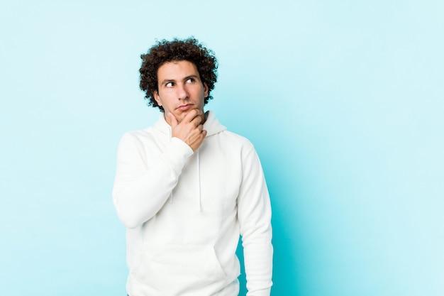 Giovane uomo sportivo contro uno sfondo blu guardando lateralmente con espressione dubbiosa e scettica.