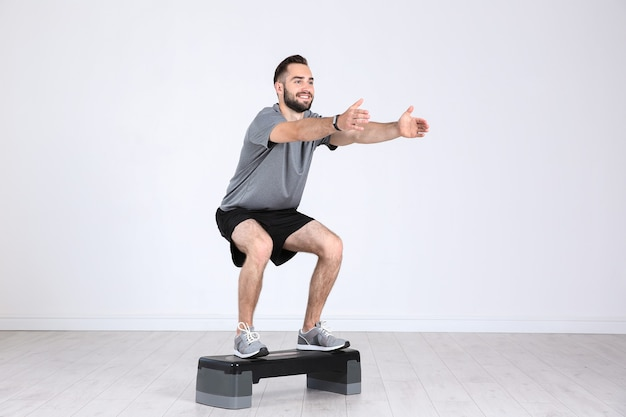 Gambe di formazione giovane uomo sportivo con stepper in palestra