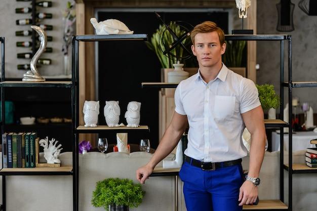 Giovane uomo sportivo in camicia bianca e pantaloni blu in piedi a casa vicino ai libri