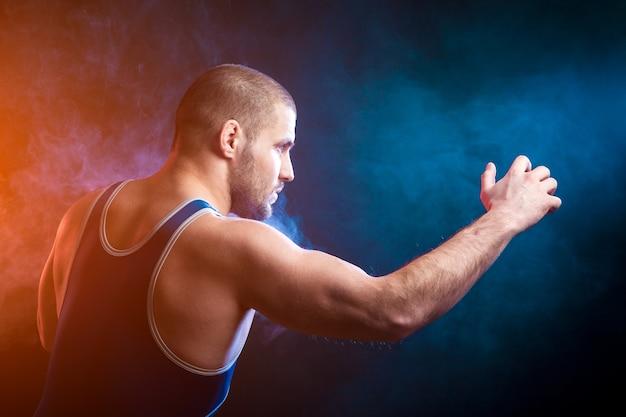 Un giovane lottatore sportivo in una maglietta sportiva verde e calzamaglia da wrestling blu che lottano contro uno sfondo di fumo blu e rosso vape su un nero isolato