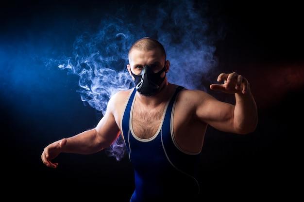 Un giovane lottatore sportivo con una maglietta sportiva verde e una maschera da allenamento che lotta contro uno sfondo di fumo blu vape su un nero isolato