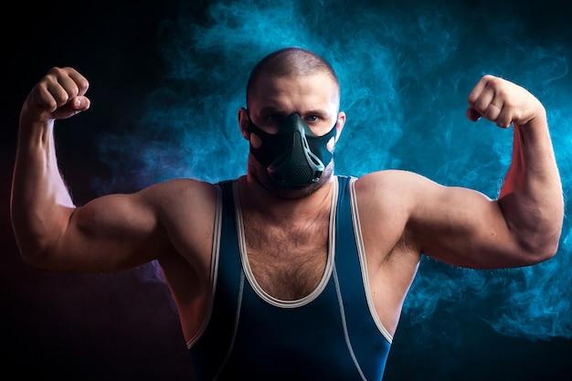 Un giovane lottatore sportivo con una maglietta sportiva verde e una maschera da allenamento in posa e mostra i bicipiti su uno sfondo di fumo blu vape su un nero isolato