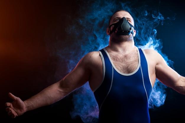 Un giovane lottatore sportivo in una maglietta sportiva verde e una maschera da allenamento in posa con le braccia piegate su uno sfondo di fumo blu vape su un nero isolato