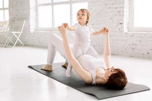 La giovani madre e neonata sportive fanno gli esercizi insieme in palestra. sviluppo sano di genitori e figli, fitness e relax