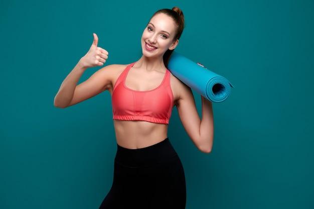 Giovane donna sportiva e sorridente in abiti sportivi che tiene in mano un tappetino da yoga e mostra il gesto del pollice in su
